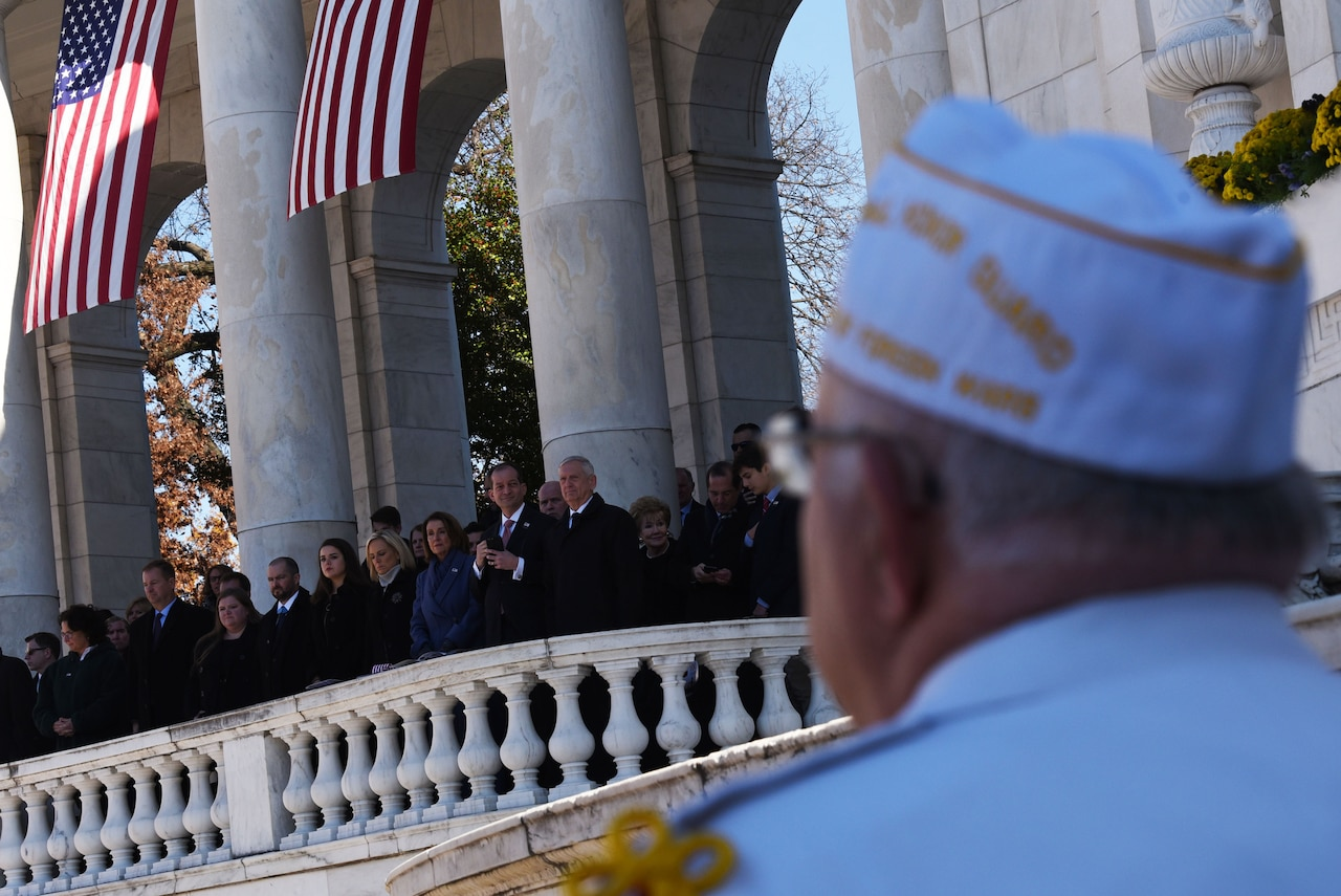 A veteran looks at the defense leaders standing on the balcony of the Memorial Amphitheater at Arlington National Cemetery