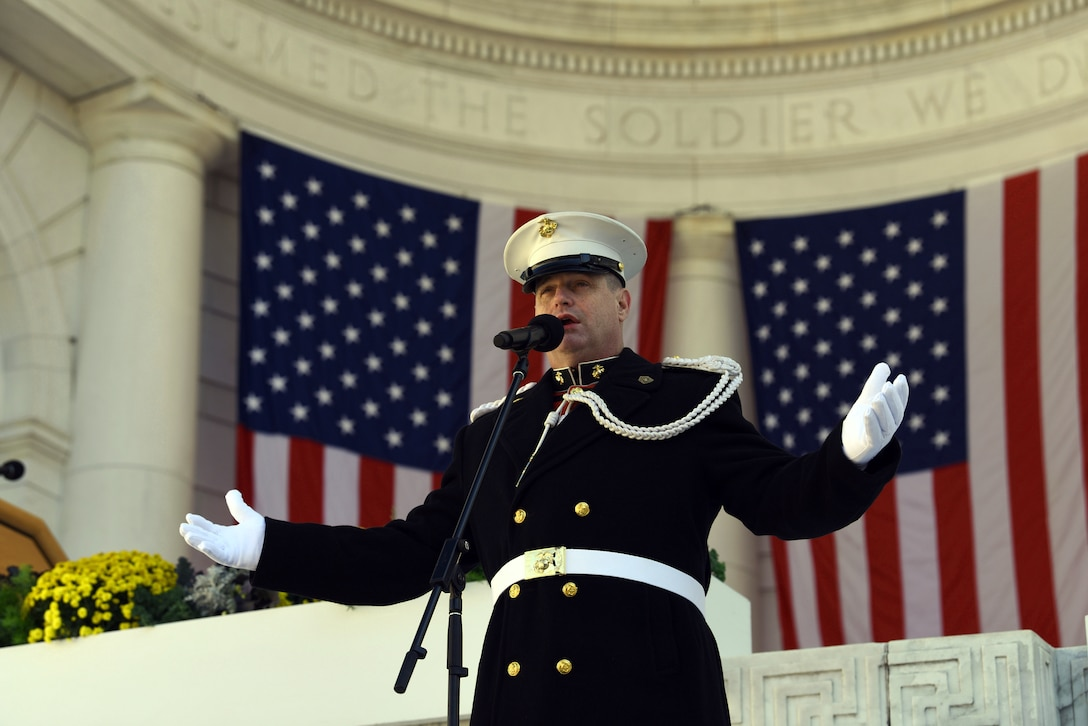 A Marine, standing, sings a song