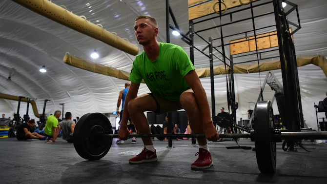 Staff Sgt. Patrick Bierman, 386th Expeditionary Force Support Squadron rations water non-commissioned officer in charge, prepares to execute a squat clean at an undisclosed location in Southwest Asia. Bierman participated in a weightlifting event on Oct. 27, 2018, to raise awareness for the fight against cancer. (U.S. Air Force photo by Staff Sgt. Christopher Stoltz)