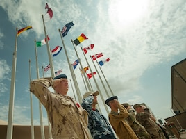 A group of multinational service members render a salute during a Service of Remembrance Nov. 11, 2018, at Al Udeid Air Base, Qatar. Members of the Royal Air Force hosted the event, organizing the involvement of 15 nations' military members. The service marked 100 years since the end of World War I. (U.S. Air Force photo by Tech. Sgt. Christopher Hubenthal)