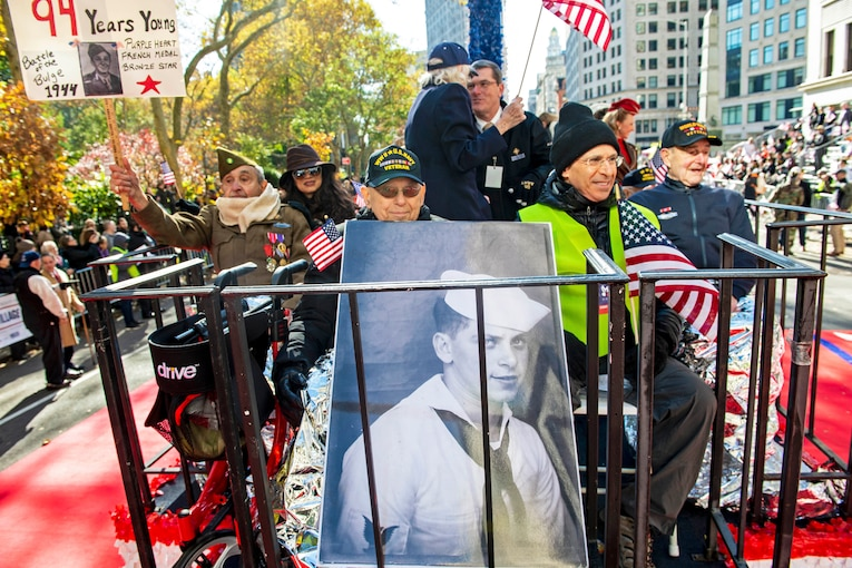 World War II veterans ride on a float during a parade while spectators watch.