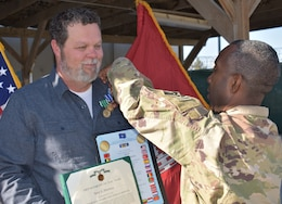 """Afghanistan District Commander, Colonel Jason Kelly presents Terry """"Hawk"""" Hawkins with the NATO, Global War on Terrorism, and Commanders award for civilian service as the District bids him farewell and Tulsa District receives their team member back."""