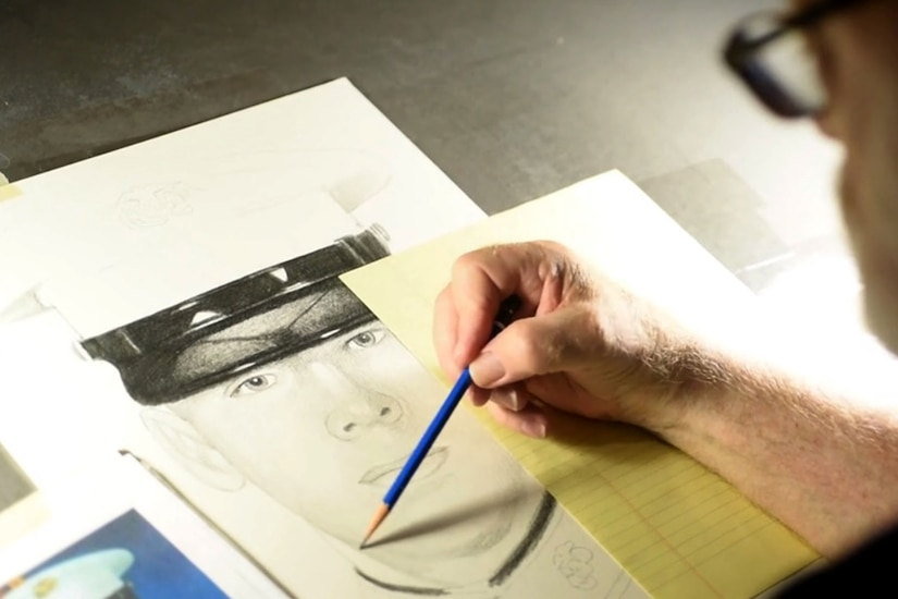 A man has a pencil to paper, drawing a portrait based on a photo of a fallen service member that sits beside the drawing pad.