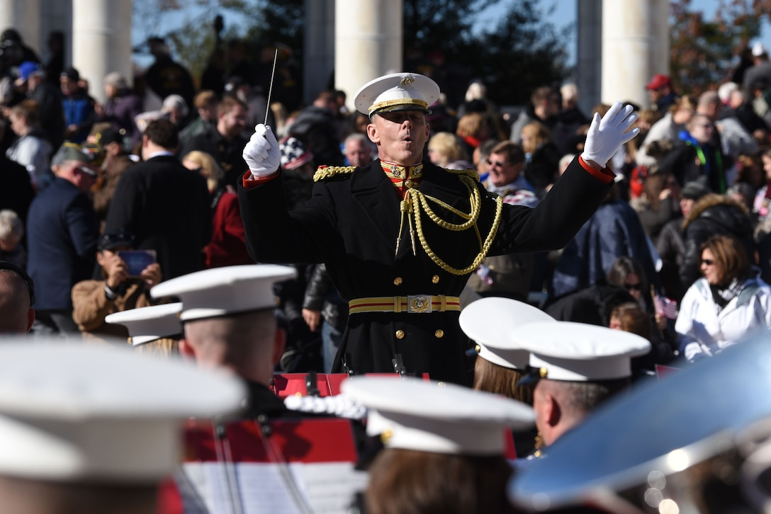 U.S. Marine Corps  band conductor stands with arms raised  in front of a band