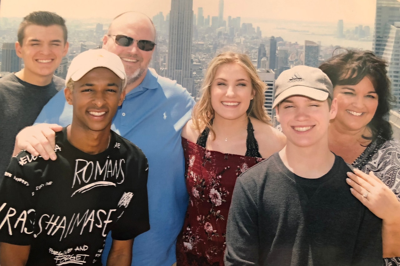 4 teens pose with parents on roof in New York City
