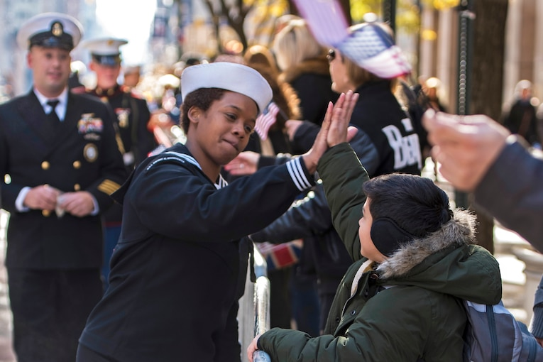 A sailor high-fives a boy along a parade route.