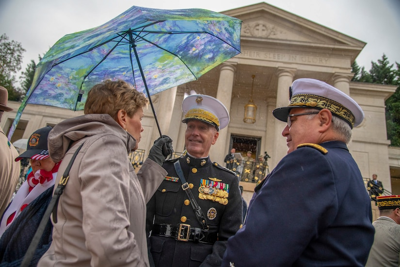 Marine Corps Gen. Joe Dunford, chairman of the Joint Chiefs of Staff, stands next to a woman holding an umbrella and a man