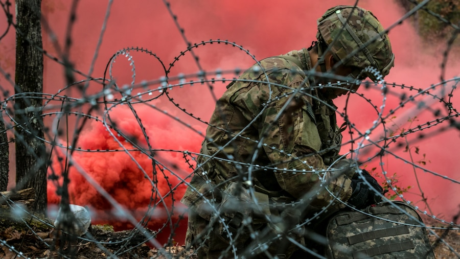 A combat medic kneels on ground working on equipment with red smoke in the background