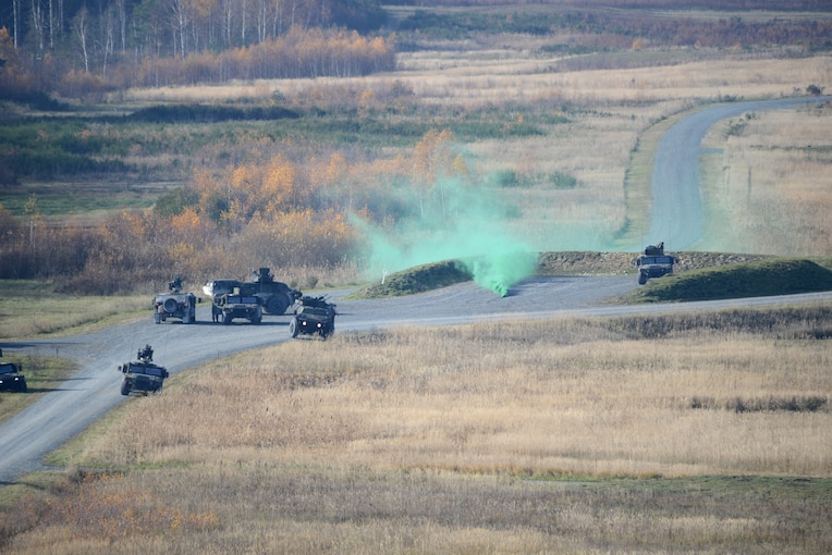 Military vehicles drive on road dotted with wafts of green smoke