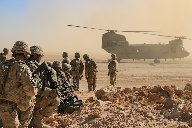 A group of troops line up behind helicopter
