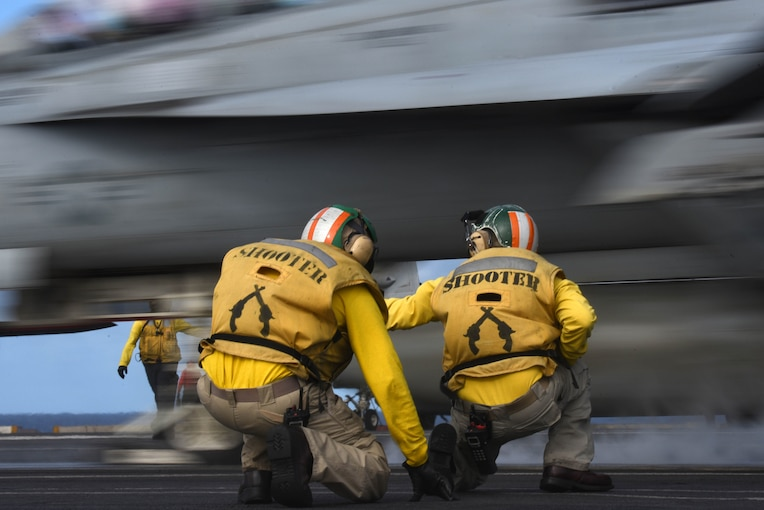 Two men kneel underneath aircraft during launch