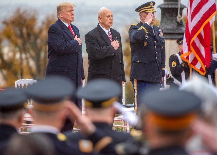 President Trump and another man stand on a dais holding their hands over their hearts while another man in uniform is saluting