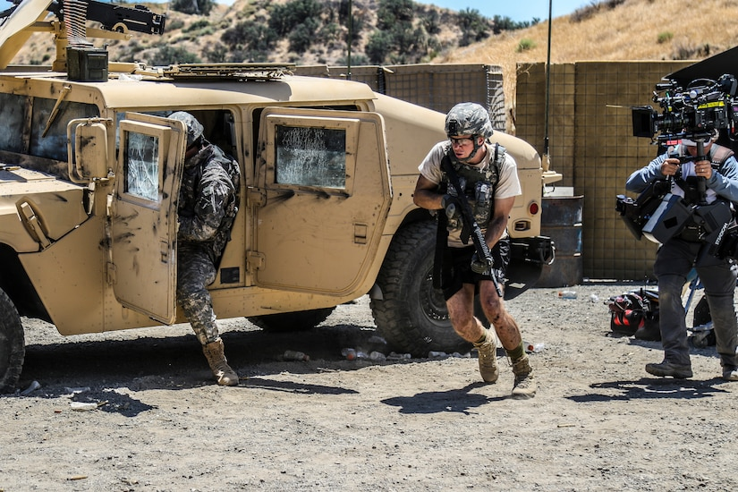 Actors portraying soldiers rush out of a Humvee.