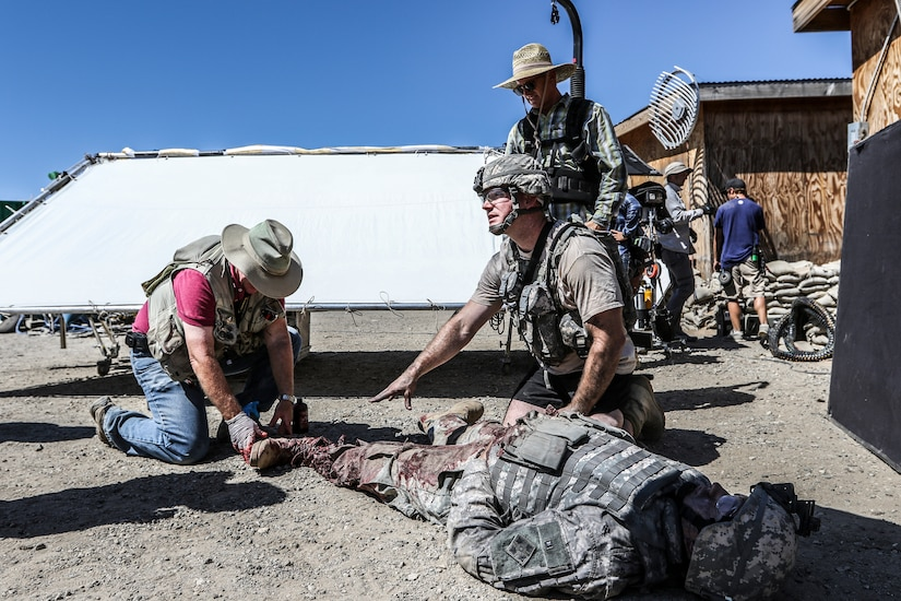 An actor kneels over a stuntman portraying an injured soldier.