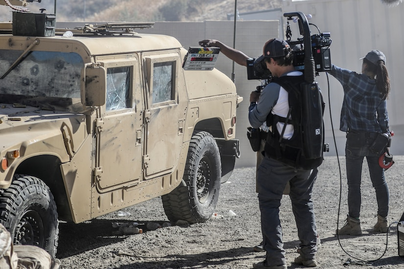 A camera operator films a slate at the start of a scene with a Humvee.