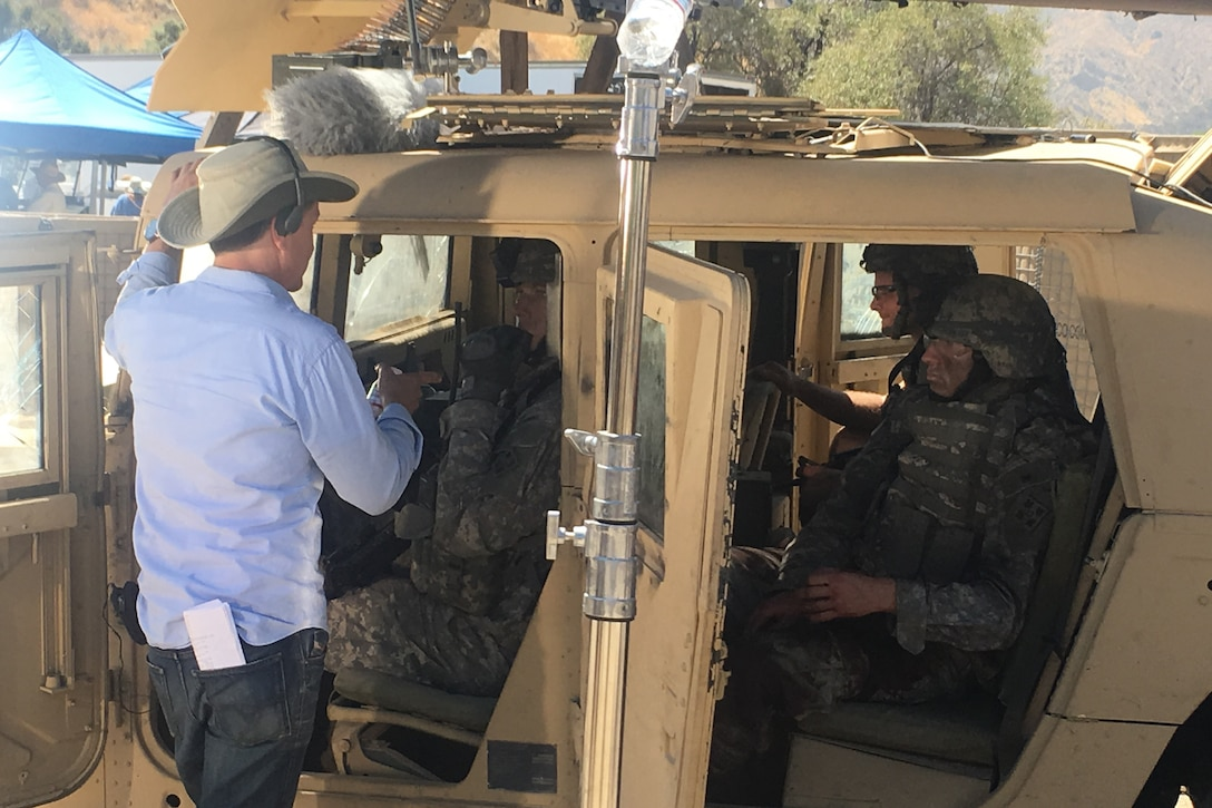 A director stands by a Humvee talking to actors inside portraying soldiers.