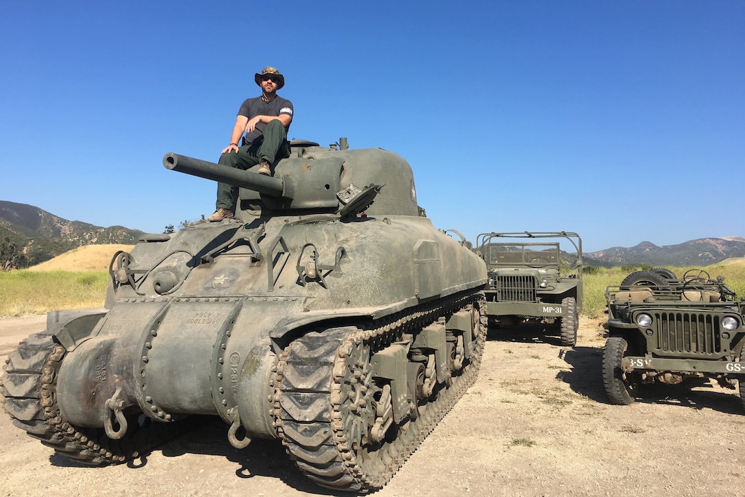 A man sits atop a WWII-era Army tank.