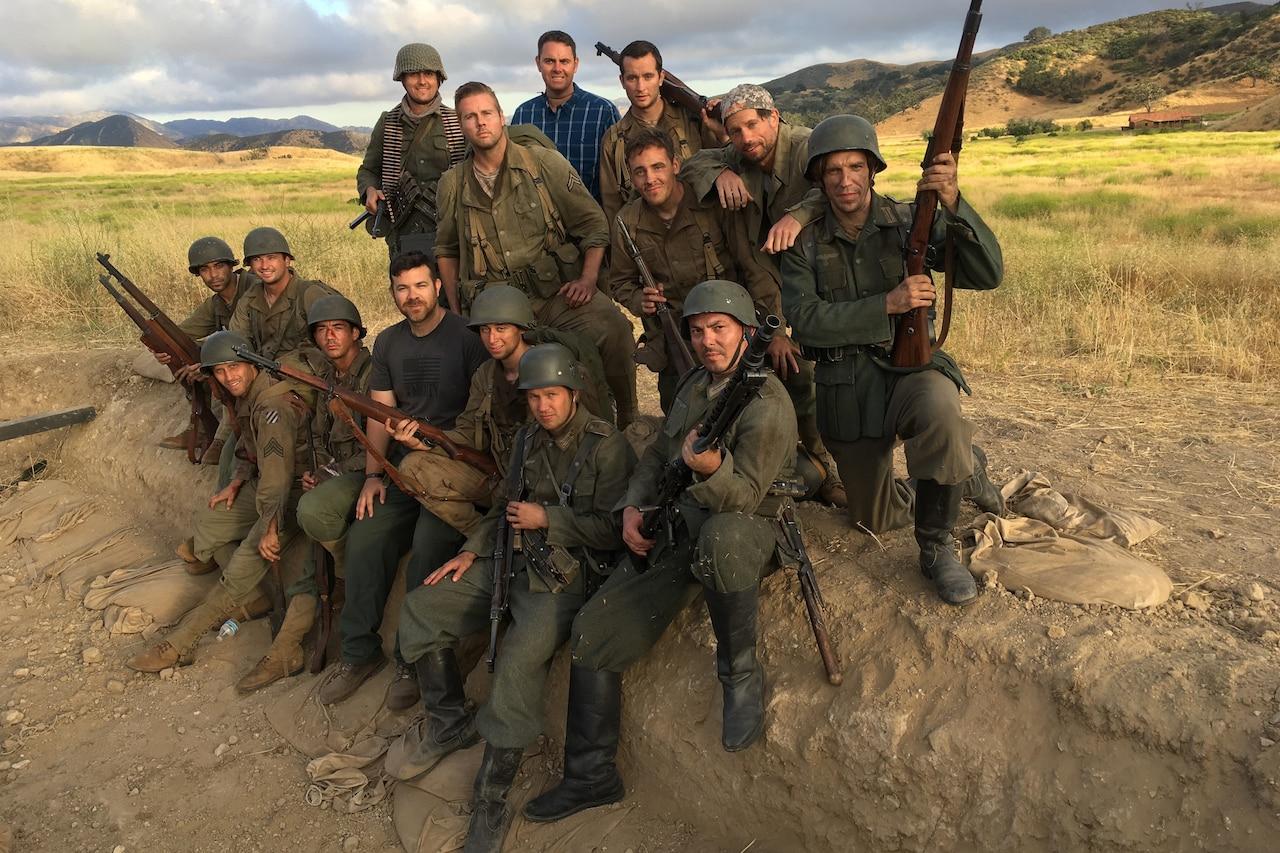 Men dressed as World War II soldiers pose in field.