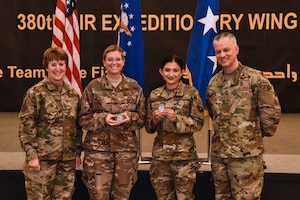 U.S. Air Force Lt. Gen. Dorothy Hogg, AF Surgeon General, and Chief Master Sgt. Steven Cum, Chief of Medical Enlisted Force and Enlisted Corps Chief, pose with two Airmen from the 380th Expeditionary Medical Group during an all-call at Al Dhafra Air Base, United Arab Emirates, Nov. 11, 2018. The Airmen were coined because of their outstanding performance and contribution to the 380th Air Expeditonary Wing mission. (U.S. Air Force photo by Senior Airman Mya M. Crosby)