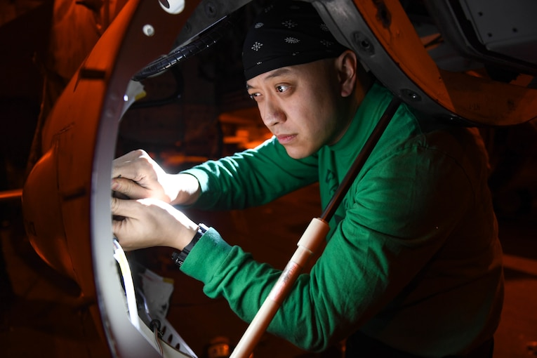 A technician works on aircraft panel