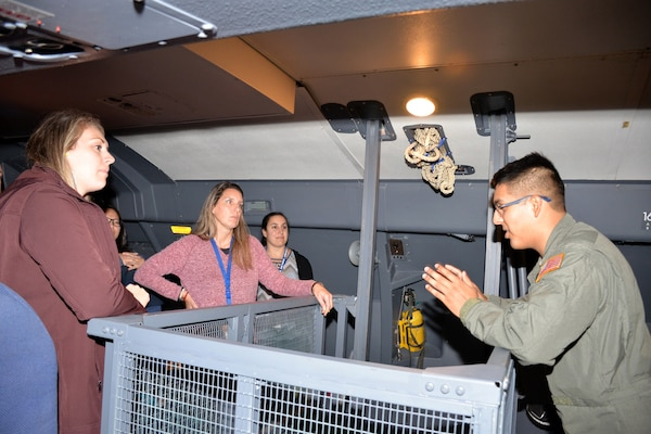 Senior Airman Andres Terrazas, 68th Airlift Squadron loadmaster, explains how crew and passengers operate in the troop compartment of a C-5M Super Galaxy to a group of recruiting influencers at Joint Base San Antonio-Lackland, Texas Nov. 8, 2018.