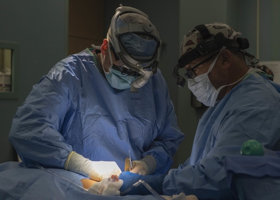 Canadian Forces Maj. Davin Schmidt, an oral surgeon from Pembroke, Ontario, performs surgery on Pedro Anton, 8, in an operating room aboard the hospital ship USNS Comfort.
