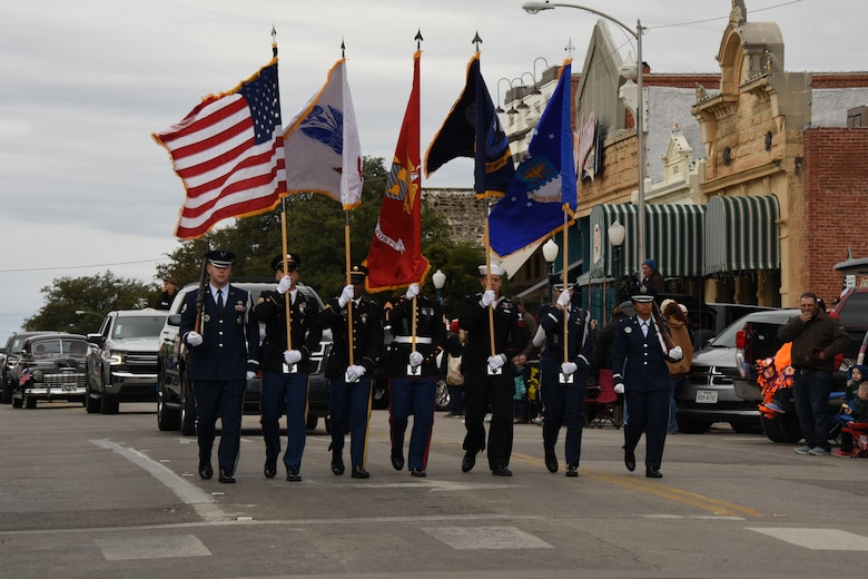 Joint Service Color Guard marches during the Veterans Day Parade in San Angelo, Texas, Nov. 10, 2018. The Joint Service Color Guard consists of members from each branch, followed by the other 400 military members participating in the parade. (U.S. Air Force photo by Airman 1st Class Zachary Chapman/Released)
