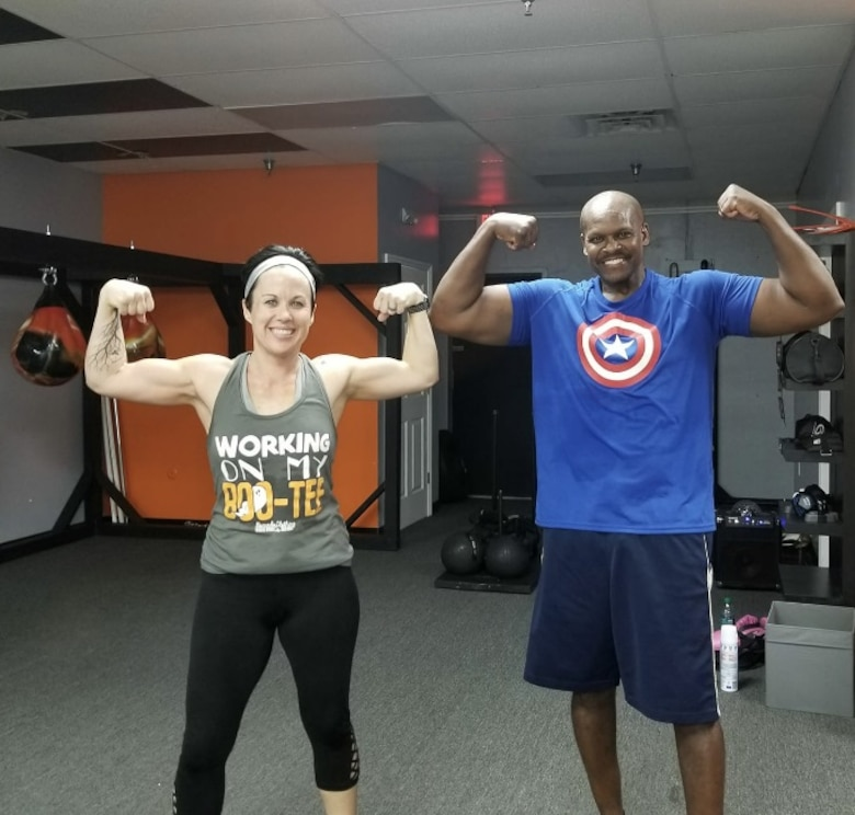 Retired Master Sgt. and financial management specialist Daryl McFadden, flexes with one of his fitness partners, Christina Millard, after a workout.  McFadden, who has survived cancer twice and undergone a triple bypass surgery, makes his health his number one priority by continuing to exercise and changing his eating habits. (Courtesy photo)