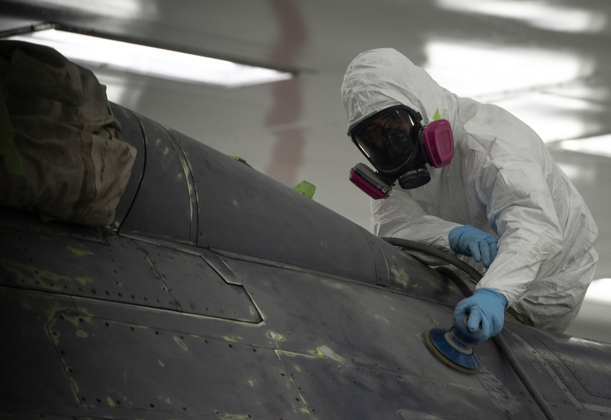 A U.S. Airman assigned to the 20th Equipment Maintenance Squadron corrosion control paint barn, sands the upper body of an F-16CM Fighting Falcon at Shaw Air Force Base, S.C., Nov. 13, 2018.