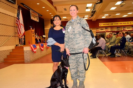 Christina Rather (left), principal at Dolph Briscoe Middle School in San Antonio, Texas, and Tech. Sgt. Melissa Proscia, 433rd Airlift Wing command post, and TThunder, a five-month old Belgian Malinois puppy from the Military Working Dog program at Joint Base San Antonio-Lackland, Texas, take a moment prior to the school's 9th annual Veterans Day ceremony.