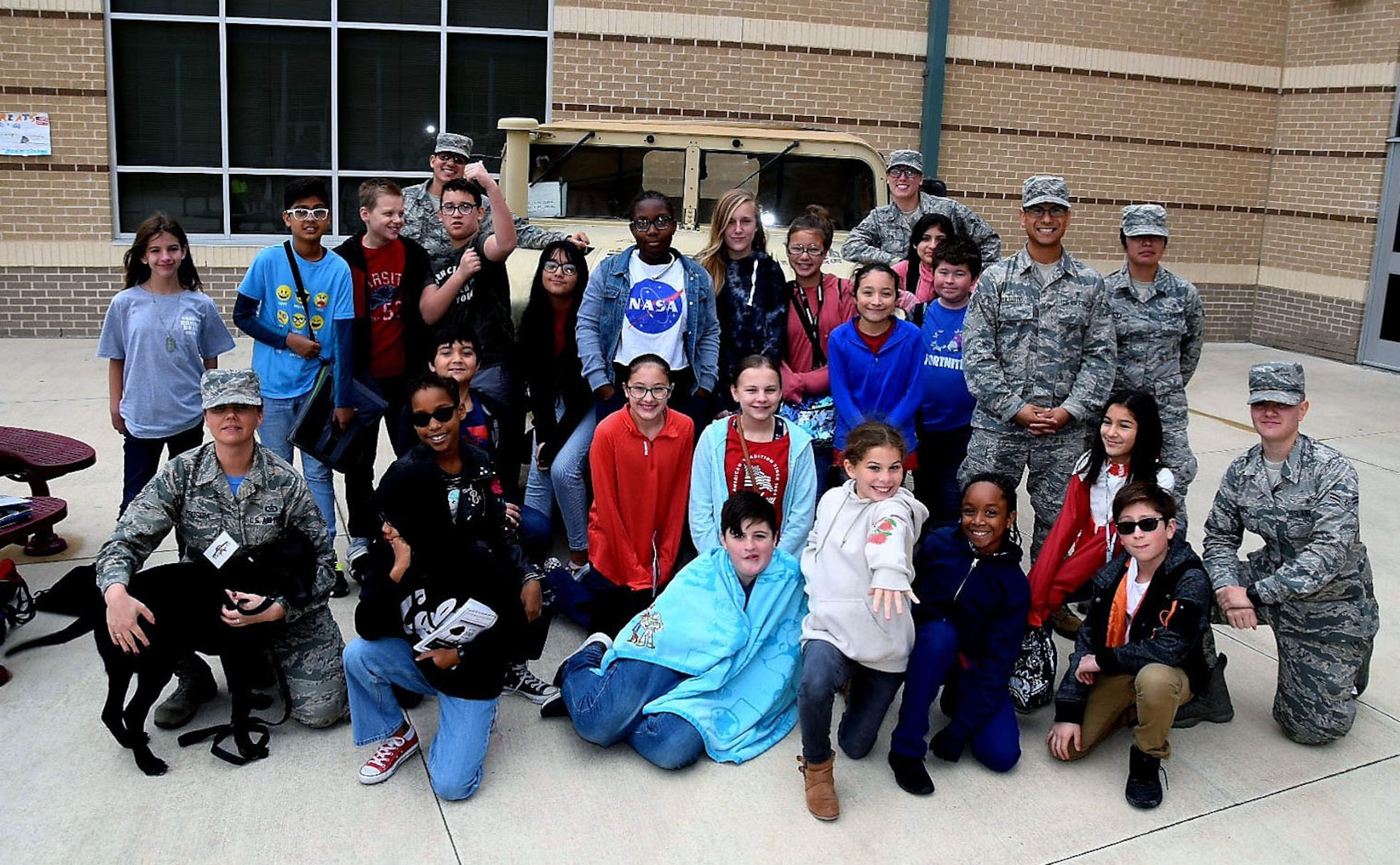 Dolph Briscoe Middle School students and Reserve Citizen Airmen with the 433rd Aeromedical Evacuation Squadron accompanied by Tech. Sgt. Melissa Proscia (left), 433rd Airlift Wing command post, and TThunder, a puppy from the Military Working Dog Program, take a moment with students after the school's 9th annual Veterans Day ceremony in San Antonio, Texas Nov. 9, 2018.