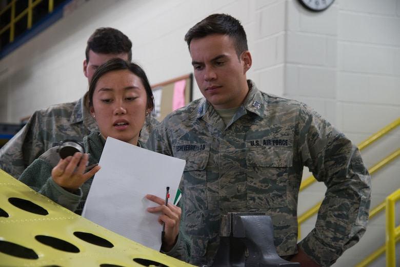 Cadets Mai-Lin Quinto and Lucas Echeverry, from the U.S. Air Force Academy, Colorado, inspect a tool designed to measure the depth of corroded pits on aircraft metals Oct. 23, 2018, at Peterson Air Force Base, Colorado.