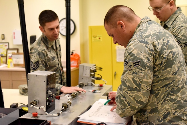 Airman 1st Class Joshua Sandoval, center, a 365th Training Squadron fundamentals of avionics students, looks through a schematic as he troubeshoots an issue during a training session at Sheppard Air Force Base, Texas, Nov. 8, 2018. Sandoval, who holds a degree in aviation maintenance technology through Eastern New Mexico University-Roswell, was able to fast-track the 39-academic-day course in less than a week and continue his training in electronic countermeasures. Also pictured is instructor Tech. Sgt. Andrew Post and student Senior Airman Stephen McCormick. (U.S. Air Force photo by John Ingle)