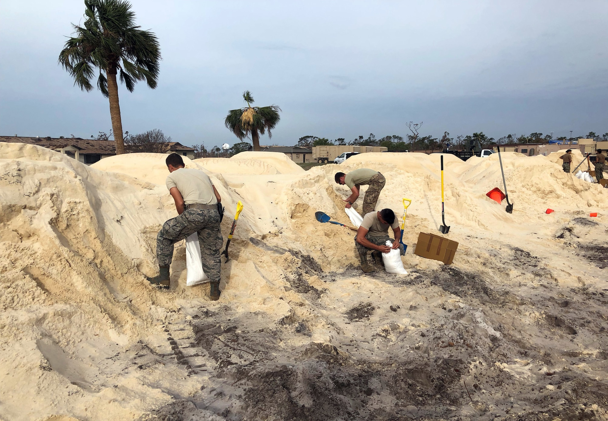 From left: Staff Sgt. Charlie Hegwer, Tech. Sgt. Skyler Shull and Airman Hunter Benson, 85th Engineering Installation Squadron, fill sandbags to place around tents in preparation of inclement weather at Tyndall Air Force Base, FL. The Airmen are part of a five-team team helping restore communication capabilities to the base after Hurricane Michael made landfall along the Florida Gulf Coast in mid-October. (U.S. Air Force courtesy photo)