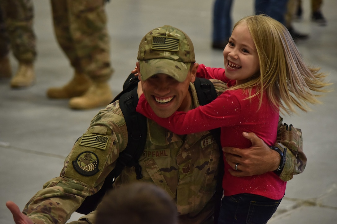 An Airman from the 819th Rapid Engineer Deployable Heavy Operational Repair Squadron Engineers (RED HORSE) hugs his children Nov. 5, 2018, at the airfields located on Malmstrom Air Force Base, Mont. The 819th RED HORSE U.S. Africa Command team shared in multi-agency base building efforts for Air Base 201 in Agadez, Niger, an expeditionary installation being constructed in one of the most remote regions in Africa. (U.S. Air Force photo by Airman 1st Class Jacob M. Thompson)