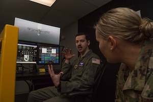 U.S. Air Force Staff Sgt. Logan Lord, a boom operator assigned to the 54th Air Refueling Squadron, explains the process of students using the KC-135 Boom Operator Weapon System Trainer simulator to U.S. Air Force Tech. Sgt. Kristie Collins, the pipeline training manager for the Air Force Personnel Center Career Enlisted Aviators assignment branch,