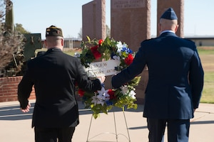 two men holding a wreath