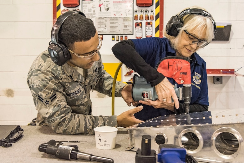 Airman 1st Class Reynaldo Rodriguez, 436th Maintenance Squadron aircraft structural maintenance journeyman, watches Yvonne Batts, Air Mobility Command civic leader from Dyess Air Force Base, Texas, install a rivet on a simulated aircraft part Nov. 7, 2018, at Dover Air Force Base, Del. Batts installed the rivet during her tour of the Fabrication Flight. (U.S. Air Force photo by Roland Balik)
