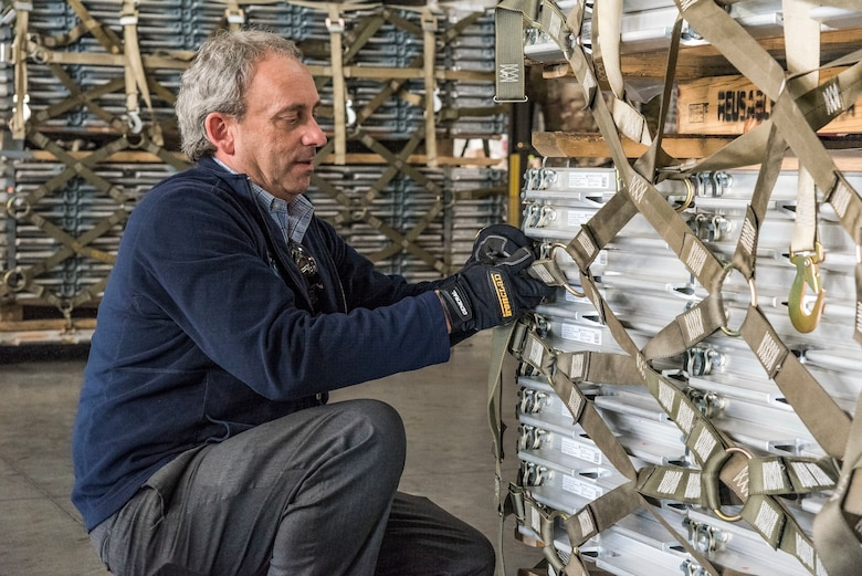 """Todd Mielke, Air Mobility Command civic leader from Fairchild Air Force Base, Wash., secures cargo netting on a  pallet Nov. 7, 2018, at Dover Air Force Base, Del. Near the end of their tour of the 436th Aerial Port Squadron, Mielke and other civic leaders were divided into teams and participated in a contest to determine who could properly attach cargo netting on a pallet under the guidance of """"Port Dawgs."""" (U.S. Air Force photo by Roland Balik)"""