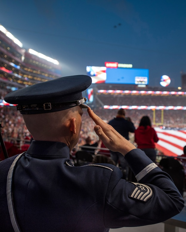 A musician with the U.S. Air Force Band of the Golden West from Travis Air Force Base, California, salutes during pregame activities of the San Francisco Forty-Niners and New York Giants Monday Night Football game at Levi's Stadium in Santa Clara, California, Nov. 12, 2018. The band performed in honor of Veterans Day and to support the National Football League's Salute to Service Campaign. (U.S. Air Force photo by Louis Briscese)