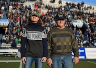 U.S. Air Force Lt. Col. Aasta Pedersen, 633rd Surgical Operations Squadron surgeon, and retired U.S. Navy Senior Chief Petty Officer Eric Pedersen, stand on Foreman Field during a Veterans Day tribute at Old Dominion University in Norfolk, Virginia, Nov. 10, 2018.