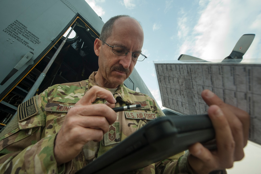 U.S. Air Force Reserve Chief Master Sgt. Kenneth Kunkel, 746th Expeditionary Airlift Squadron flight engineer, processes paperwork for a C-130 Hercules pre-flight inspection Nov. 13, 2018, at Al Udeid Air Base, Qatar. Kunkel reached 10,000 flying hours Oct. 6, 2018 a number considered prestigious amongst military aviators. (U.S. Air Force photo by Tech. Sgt. Christopher Hubenthal)