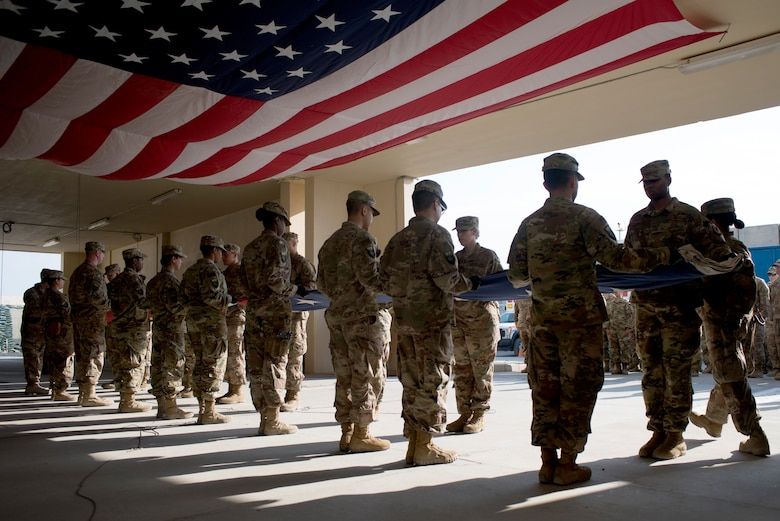 On Veterans Day, Col. Robert York, commander of the 455th Expeditionary Medical Group at Bagram, led a group of Airmen in a ceremony to remove and replace the large flag that hangs at the Craig Joint Theater Hospital Nov. 11.