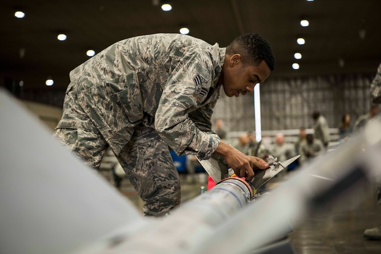 U.S. Air Force Senior Airman Travonne Lindsay, a 13th Aircraft Maintenance Unit weapons load crew member, inspects an armament during the third quarter load competition at Misawa Air Base, Japan, Nov. 9, 2018. Team Misawa members from the 13th AMU and 14th AMU compete every quarter on their ability to quickly and properly arm their respective aircrafts with munitions. (U.S. Air Force photo by Airman 1st Class Collette Brooks)
