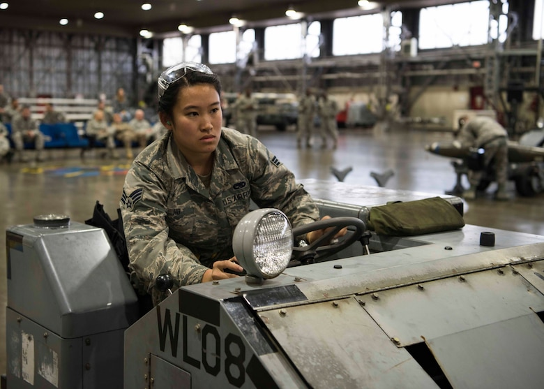 U.S. Air Force Senior Airman Jessica Ho, a 14th Aircraft Maintenance Unit load crew member, drives a MJ-1 standard lift truck during the third quarter load competition at Misawa Air Base, Japan, Nov. 9, 2018. Airmen use this rear-steered transportation device to align bomb lugs into the bomb rack hooks on F-16 Fighting Falcons, requiring absolute concentration and attention to detail to prevent aircraft damage while racing against the clock. (U.S. Air Force photo by Airman 1st Class Collette Brooks)