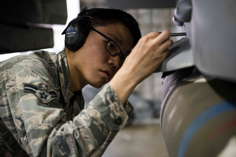 U.S. Air Force Airman 1st Class Aaron Yogi, a 14th Aircraft Maintenance Unit load crew member, performs a mechanical inspection with a pin during the third quarter load competition at Misawa Air Base, Japan, Nov. 9, 2018. This crucial step ensures loaded munitions are properly secured onto the aircraft. (U.S. Air Force photo by Airman 1st Class Collette Brooks)