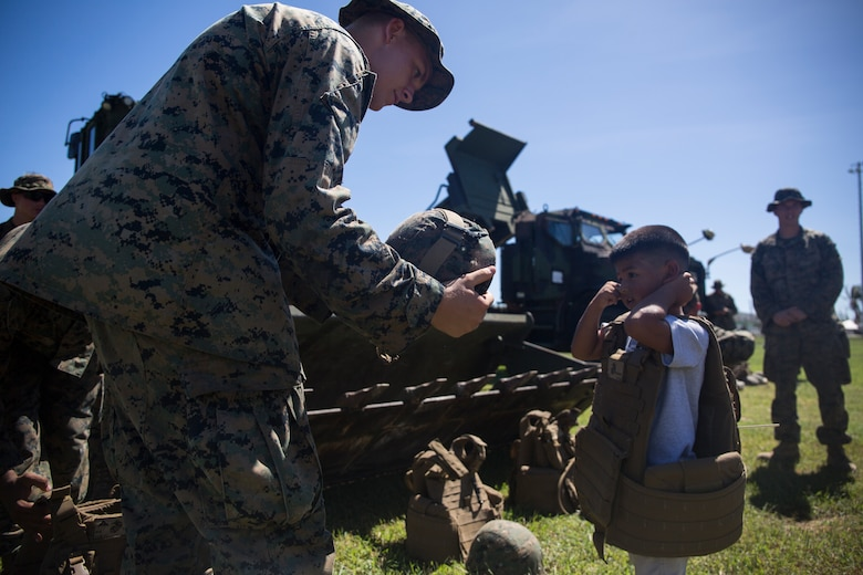 A Marine with Combat Logistics Battalion 31 helps a Tinian child into a flak jacket and helmet after a ceremony marking the end of the 31st Marine Expeditionary Unit's mission as part of the U.S. Defense Support of Civil Authorities relief efforts on Tinian, Commonwealth of the Northern Mariana Islands, Nov. 14, 2018. Marines and Sailors with the 31st MEU and CLB-31 assisted the U.S. Federal Emergency Management Agency and local and civil authorities on Tinian to deliver aid to Tinians affected by Super Typhoon Yutu, which struck here Oct. 25 as the second strongest storm to ever hit U.S. soil. Marines and Sailors with the 31st MEU and CLB-31 arrived on Tinian Oct. 29-31 to lead relief efforts on Tinian in response to Yutu as part of Task Force-West. TF-W is leading the Department of Defense's efforts to assist CNMI's local and civil authorities provide critical assistance for citizens devastated by Yutu. The 31st MEU, the Marine Corps' only continuously forward-deployed MEU, provides a flexible force ready to perform a wide-range of military operations across the Indo-Pacific region.