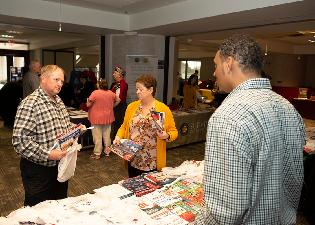 A vendor speaks with two associates during a Veterans Information Fair.