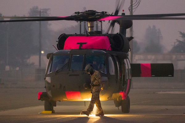 U.S. Army Sgt. Greg Fernandez, a UH-60M Black Hawk helicopter crew chief, works outside of the helicopter after landing, Nov. 11, 2018, at Sacramento Mather Airport in Mather, California. The helicopter is one of the first M-model UH-60s assigned to the California Army National Guard. The aircraft and crew traveled from Joint Forces Training Base, Los Alamitos, in Southern California to support state agencies battling the deadly Camp Fire in Northern California.