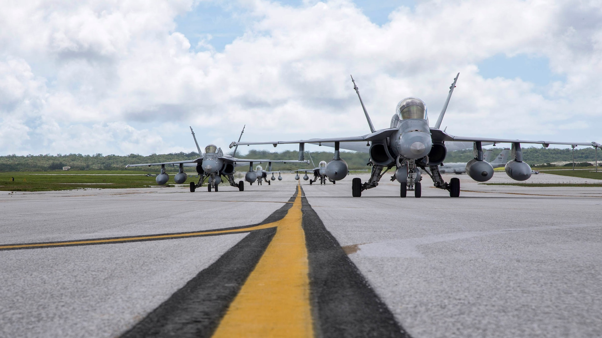 F/A-18 Hornets lined up on a flight line from a ground-level perspective.